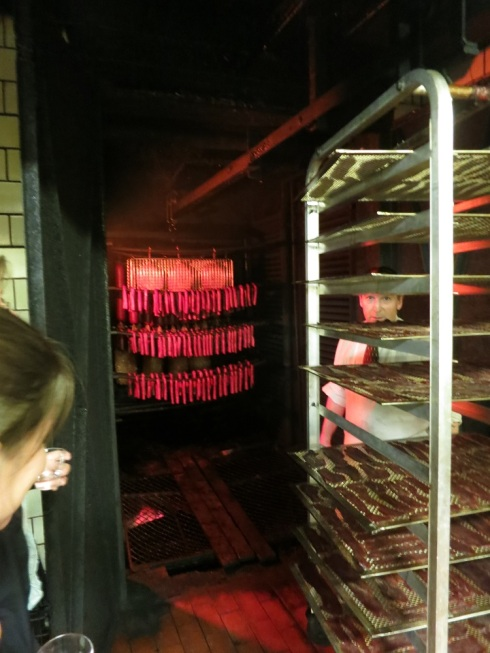Sausages, racks of bacon, and other meats, smoking away in the smoker.