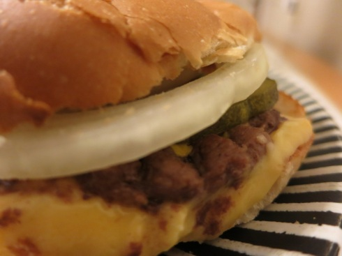 A blurry photograph of a regular cheeseburger.  It's tasty in focus or out.